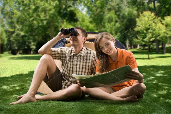 Два путешественника сидят на траве изучая местность