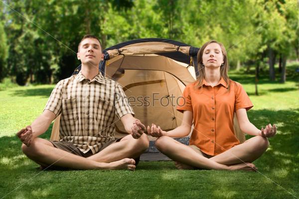 Молодая пара сидит на природе и медитирует на фоне палатки