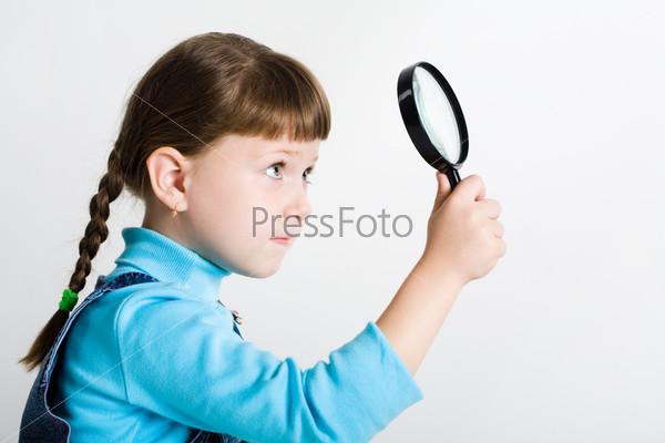 Серьезная девочка изучает что-то глядя в лупу