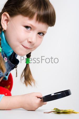 Увлеченная школьница рассматривает лист под лупой