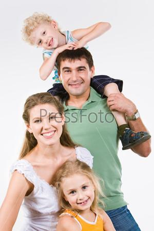 Счастливая семья смотрит в камеру и улыбается