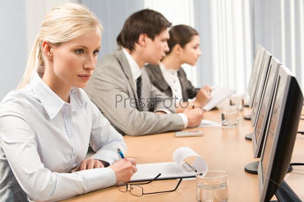 Сосредоточенная девушка сидит за монитором с ручкой в руках на фоне своих коллег