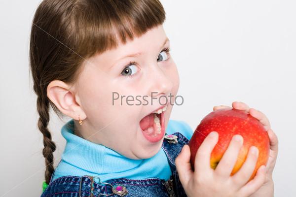 Голодная девочка раскрыв рот собирается откусить яблоко