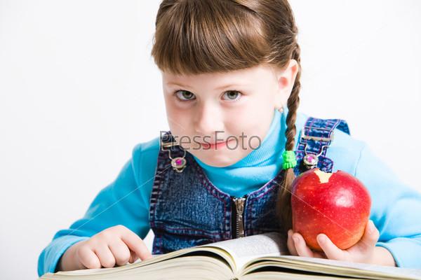 Красивая девочка читает книгу держа в руках красное яблоко