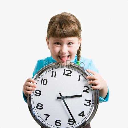 Озорная девочка показывает язык держа в руках часы