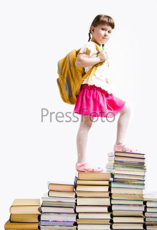 Нарядная девочка с рюкзаком поднимается по ступенькам из книг и смотрит в камеру