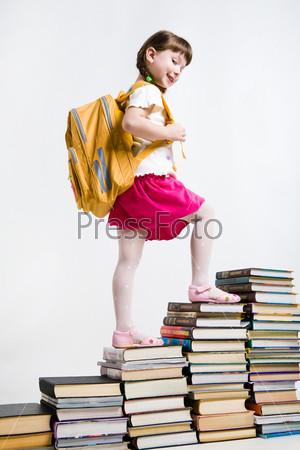 Забавная ученица шагает по книгам вверх и улыбается