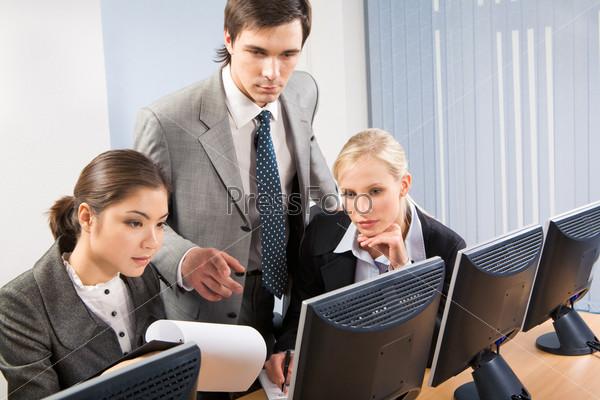 Служащие в офисе обсуждают детали рабочего проекта