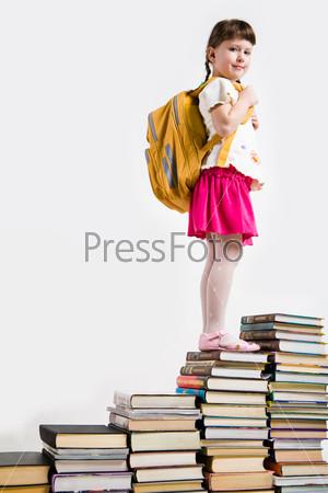 Школьница с рюкзаком стоит на стопке учебников