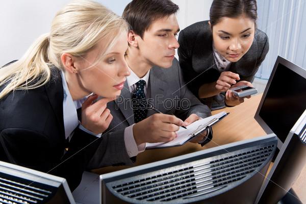 Группа сотрудников объединенных в круг смотрит в монитор компьютера
