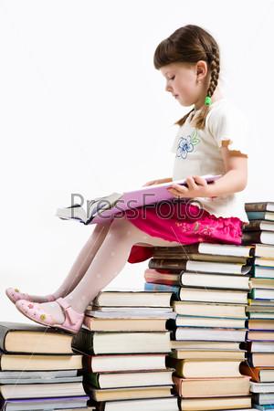 Прилежная ученица сидит на стопке книг с открытым учебником
