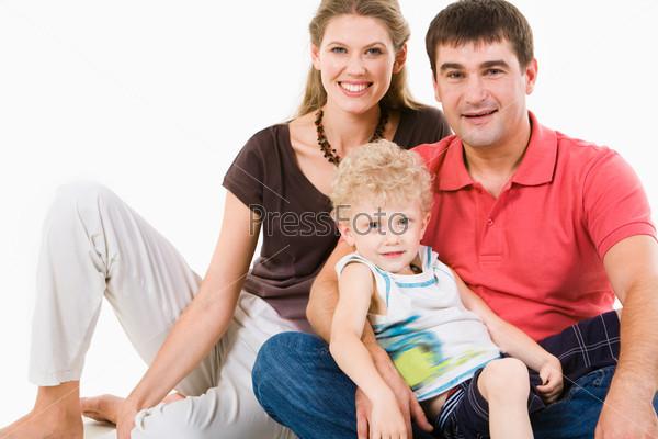 Красивая молодая пара сидит на полу со своим сыном