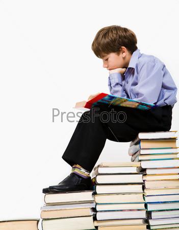 Увлеченный школьник читает книгу сидя на стопке учебников
