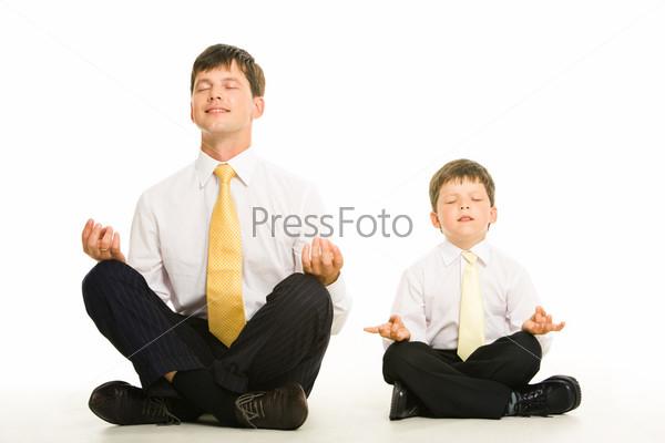 Папа с сыном в деловых костюмах сидят на полу в позе лотоса