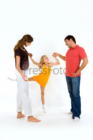 Фотография на тему Мама и папа держат за руки свою дочь выполняющую упражнение