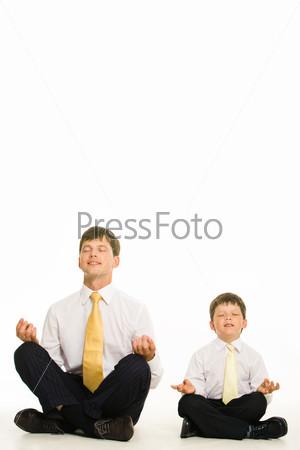 Папа и сын закрыв глаза медитируют сидя на полу