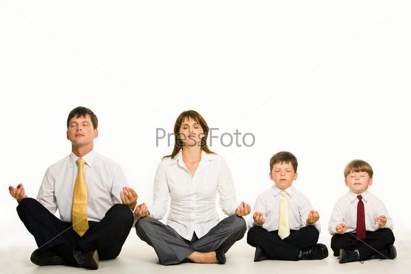 Семья из четырех человек в деловых костюмах сидит на полу и медитирует
