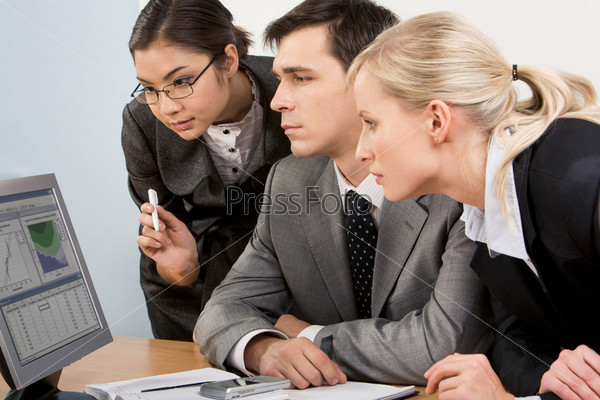 Группа сотрудников рассматривает графики на мониторе компьютера