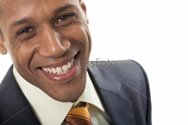 Лицо успешного афро-американского бизнесмена смотрящего в камеру с улыбкой