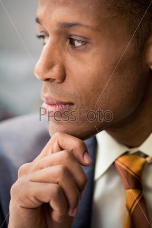 Крупный план лица задумчивого бизнесмена смотрящего в сторону