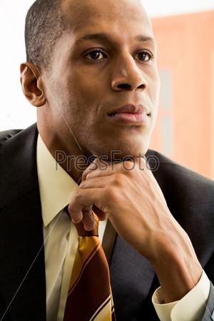 Успешный мужчина сосредоточенно смотрит в сторону