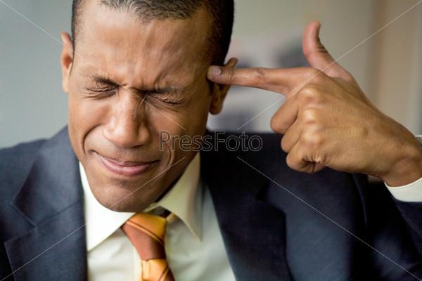 Солидный мужчина зажмурившись держит палец у виска