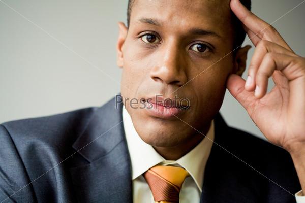 Задумчивый солидный мужчина смотрит в камеру придерживая рукой голову