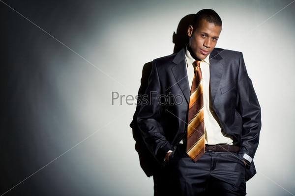 Уверенный деловой мужчина стоит у стены