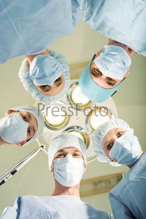 Команда хирургов в операционной смотрят в камеру