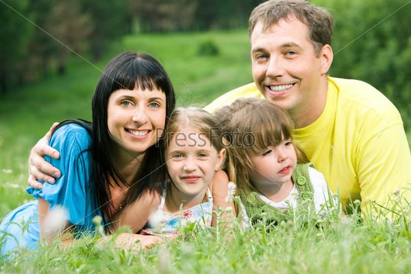 Фотография отца, счастливо обниающего свою жену и двух дочерей на природе