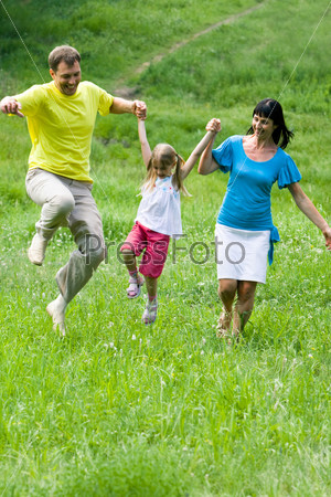 Родители играют со своей дочкой на природе, держа ее за руки
