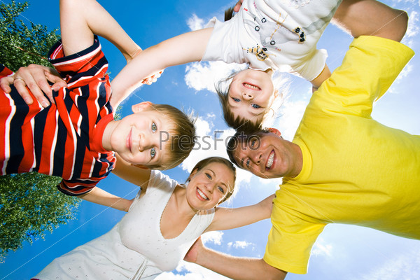View from below of happy family embracing each other and looking at camera on the background of sky
