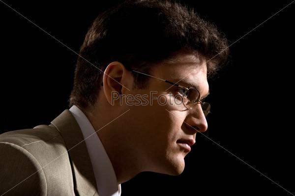 Сосредоточенный бизнесмен на черном фоне в профиль