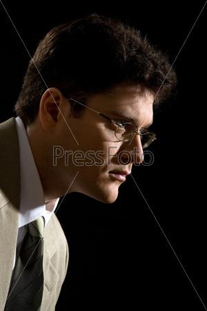 Озадаченный бизнесмен в очках смотрит в сторону на черном фоне