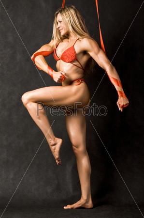 Спортивная девушка в красном купальнике стоит в профиль согнув ногу в колене