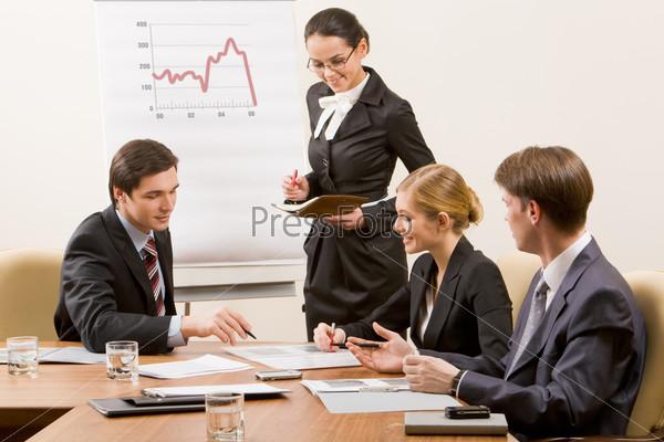 Группа коллег по работе обсуждает график изменения продаж за столом