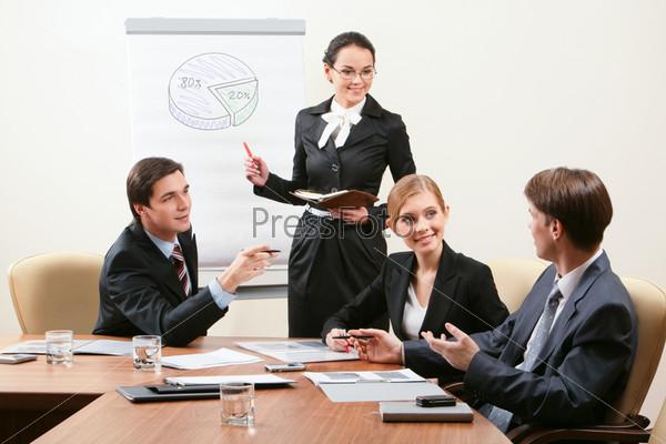 Деловая женщина объясняет диаграмму своим коллегам