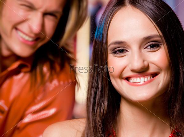 Крупный план лица довольной девушки на фоне молодого человека
