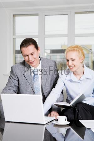 Пара сотрудников смотрят на экран ноутбука и общаются