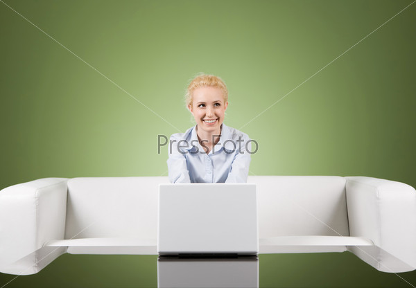 Улыбающаяся девушка сидит за ноутбуком в офисе на диване