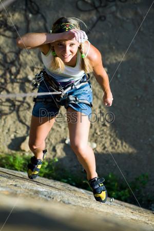Уставшая альпинистка висит над горой