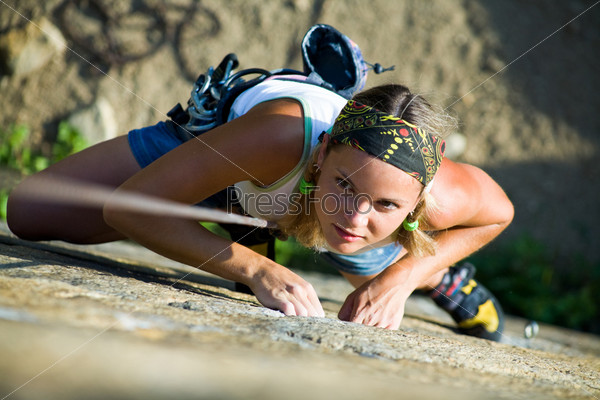 Карабкающаяся по скале девушка