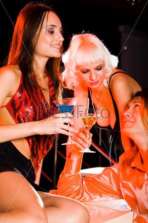 Яркие девушки на вечеринке общаются с парнем