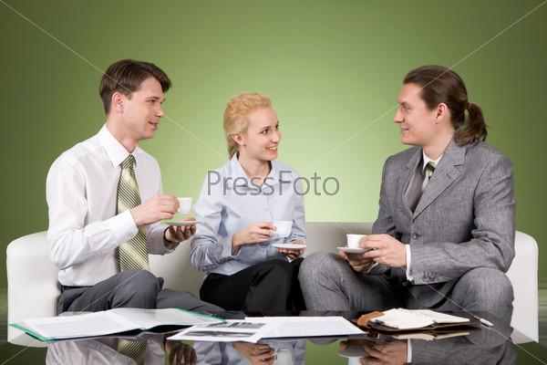 Сотрудники пьют кофе сидя на диване в офисе