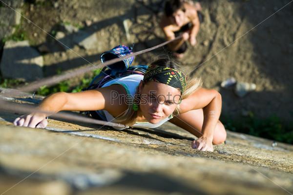 Спортсменка карабкается на вершину скалы