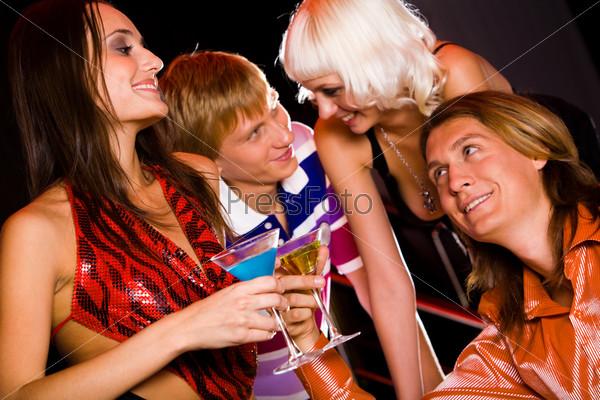 Молодые люди активно общаются в ночном клубе