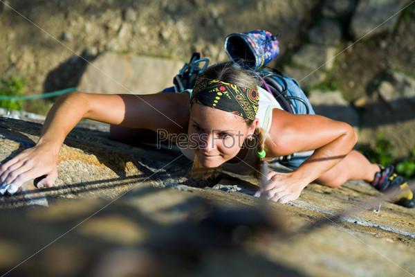 Девушка, сконцентрировавшись, поднимается по скале