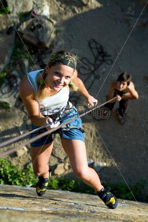 Смелая альпинистка взбирается по горе и улыбается, глядя в камеру