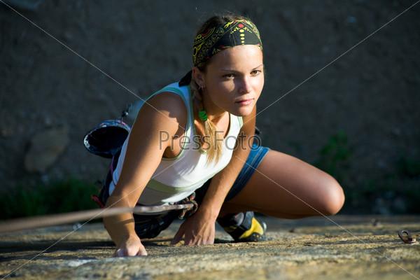 Альпинистка, взбирающаяся на вершину скалы
