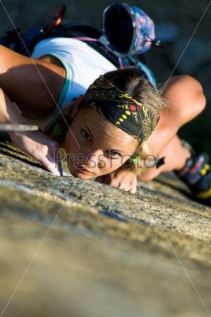 Напряженное лицо альпинистки, поднимающейся вверх по скале
